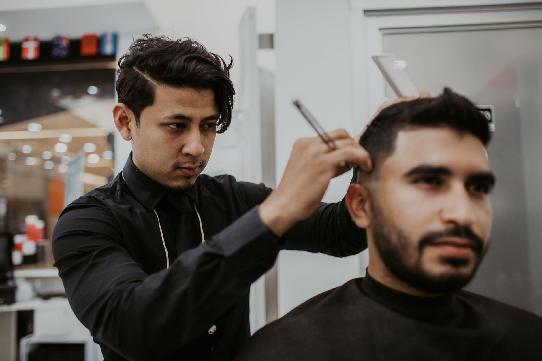 man cutting another man s hair